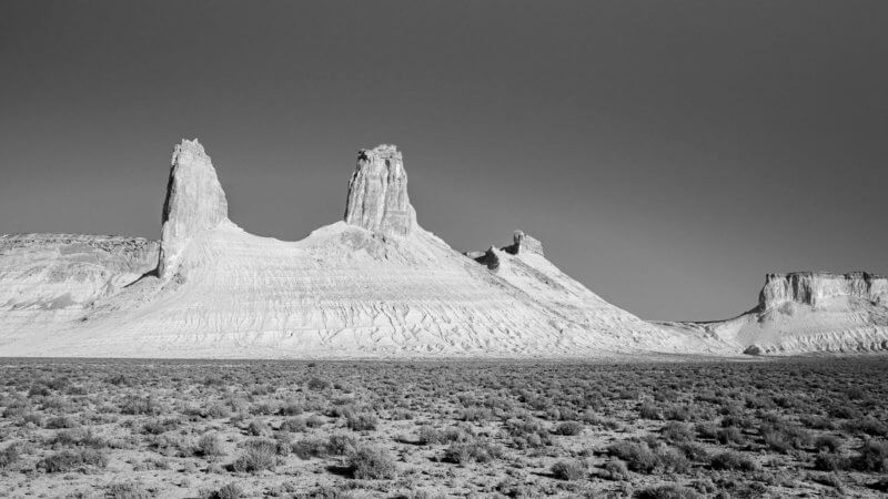 A wide shot of a chain of three towers with scrubby, flat plateau in the foreground.