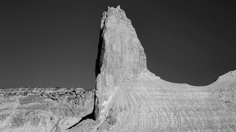 A single tower of rock with a steep promontory overlooks the Ustyurt plateau.