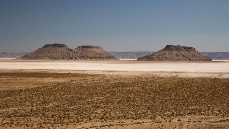 Three camel humped rocky mountains sit alone in a remote desert salt pan near Turkmenistan.