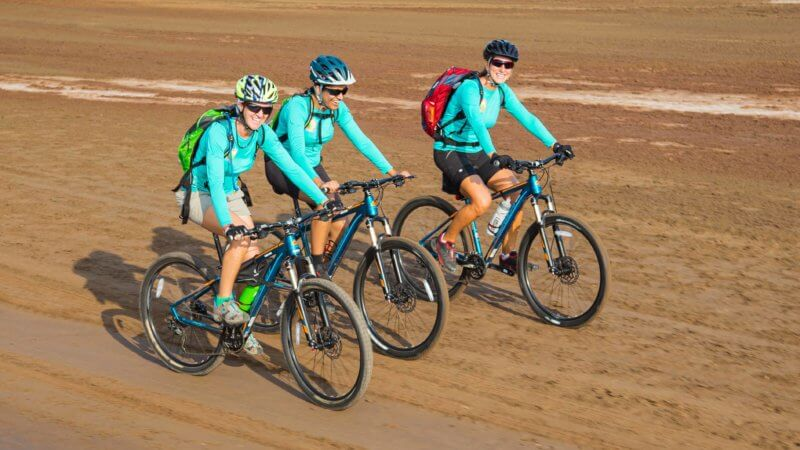 Three cyclists in blue tops cycling on sand in Dallol.