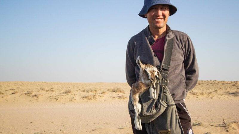 A Kazakh herder with a baby goat in the Saryesik-Atyrau Desert.