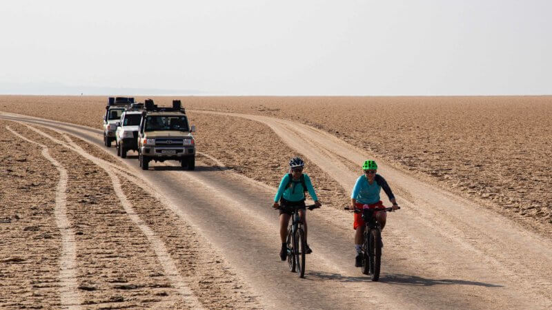 Two cyclists and three jeeps traversing a plateau in Dallol.