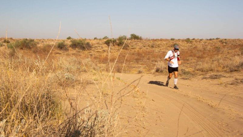English ultra-runner Jamie Maddison running across the desert sands of the Saryesik-Atyrau in Kazakhstan, south of Lake Balkhash.