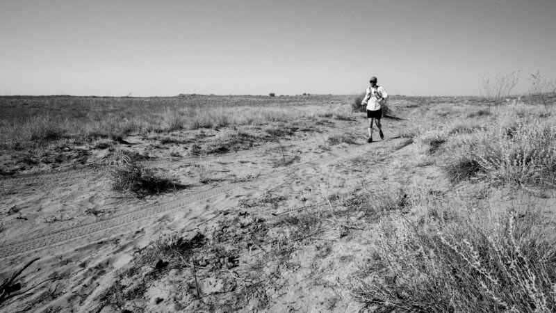 Black and white photo of Jamie Maddison running across the Saryesik-Atyrau's sandy desert track in Kazakhstan.