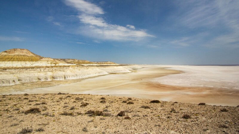 A salt pan in the Ustyurt plateau devoid of any water and beneath big, blue skies.