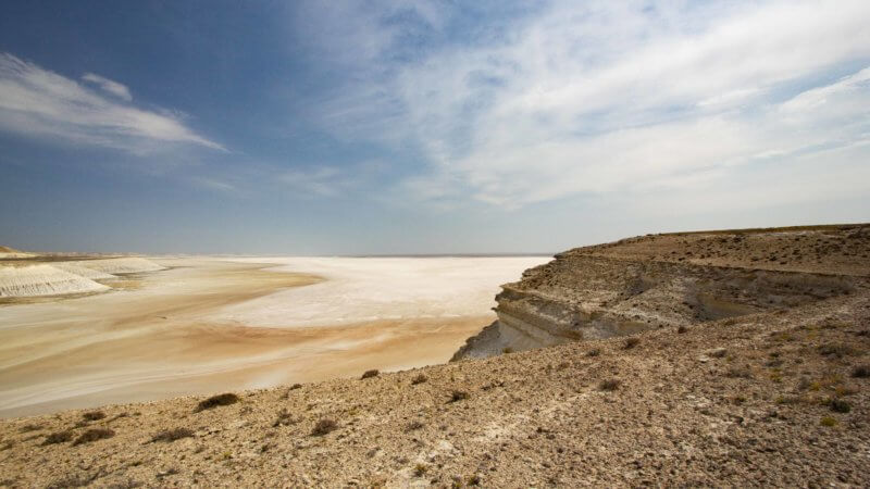 Looking down into a white salt desert pan from atop a cliff.