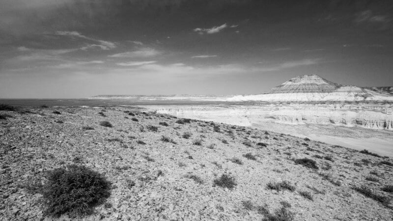 Black and white image of desert foreground and a rugged mountain overlooking an empty expanse in background.