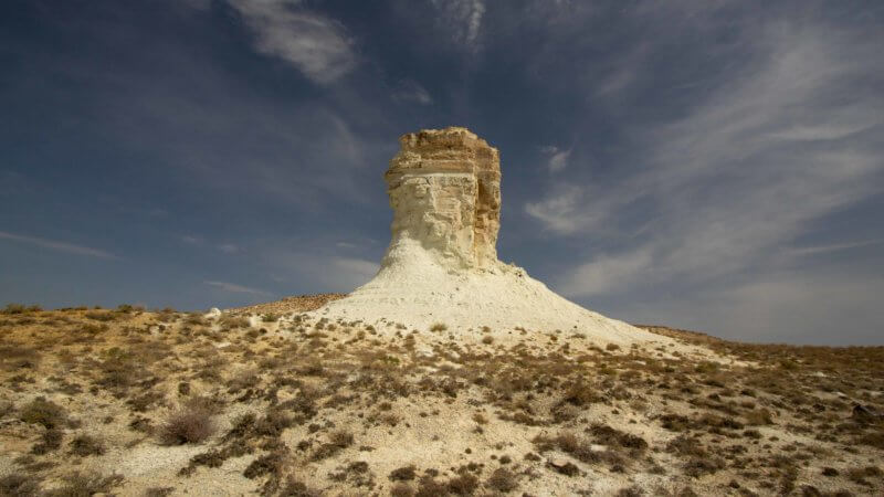 A single tower of chalk rock pokes up out of the scrubby desert landscape.