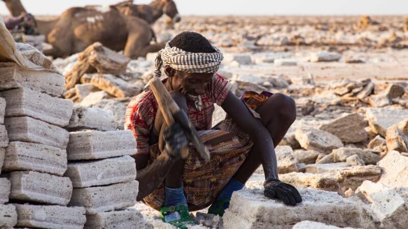 A Dallol working next to a tall stack of cut salt blocks in Dallol.
