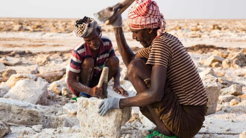 Two salt workers hacking a salt blocks with their axe tools and crouching down.