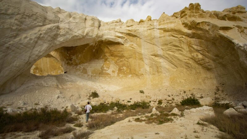 A man in a white shirt walks towards an amphitheatre of rock and a rock arch in the Ustyurt, Kazakhstan.