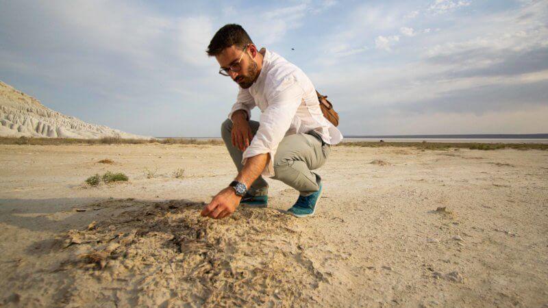 A desert explorer crouches down to inspect decayed plant matter in an Ustyurt salt pan.