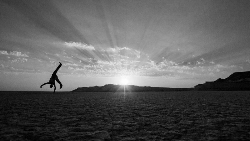 Silhouette of a man cartwheeling on a salt pan as the sun is setting.