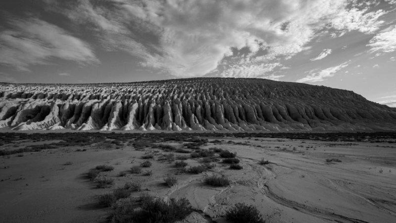 Black and white photo in Ustyurt showing complex ridges of water-worn chalk cliffs in desert.
