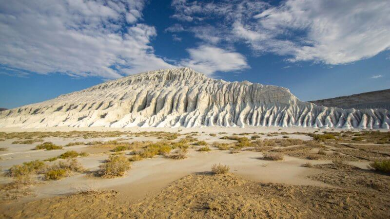 A humped, chalk white hill with weathered slopes overlooks a patch of desert.
