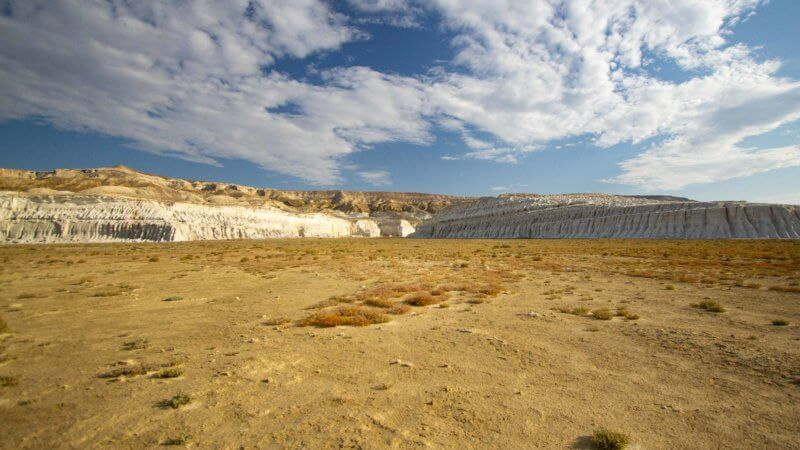 A sandy, flat expanse of Ustyurt desert in front of chalk cliffs with water worn slopes.