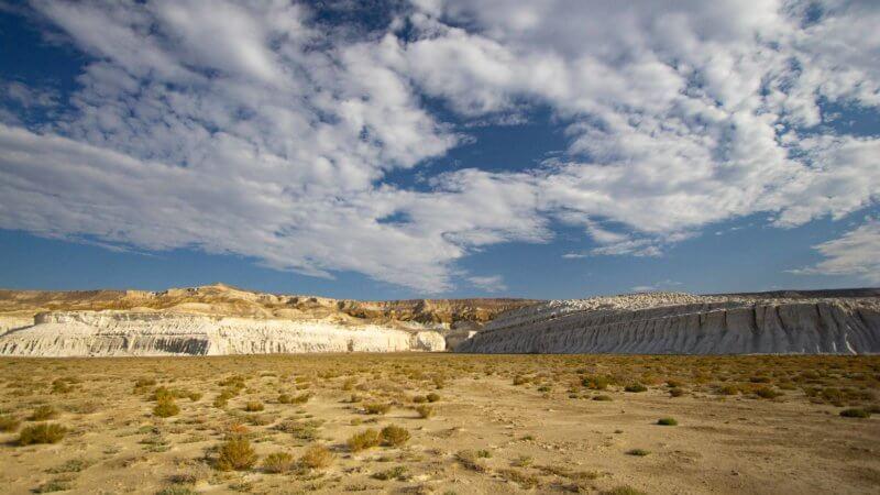Long, white chalk cliffs converge in the distance, overlooking a sandy Kazakhstan desert.