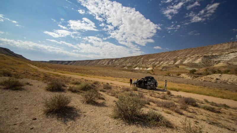 An off-road car parked on a dirt track leading up a desert valley.