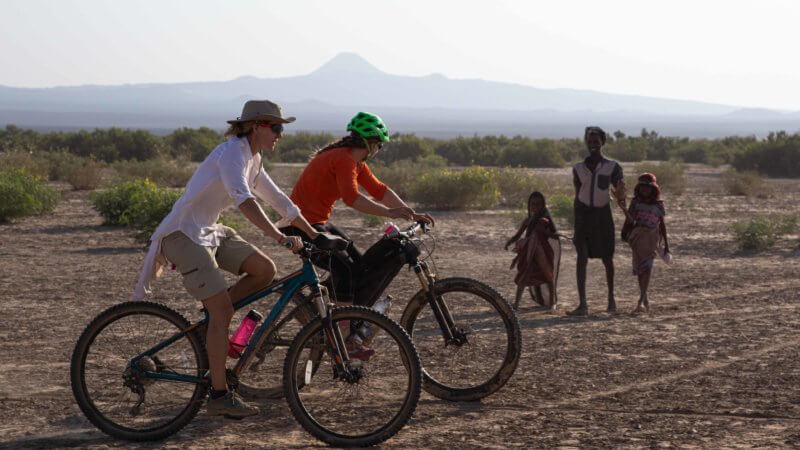 Two British cyclists pass by three Afar villages in the Danakil.