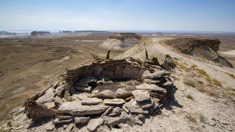 A circular shaped hunting pen formed from slab rock sits on the edge of a cliff.