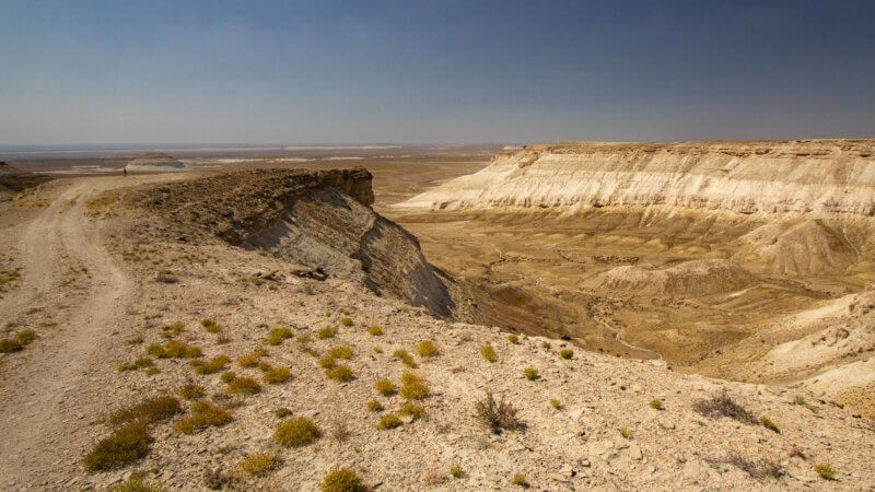 A flat escarpment leading out to a peninsula overlooking an expansive flat plateau in western Kazakhstan.