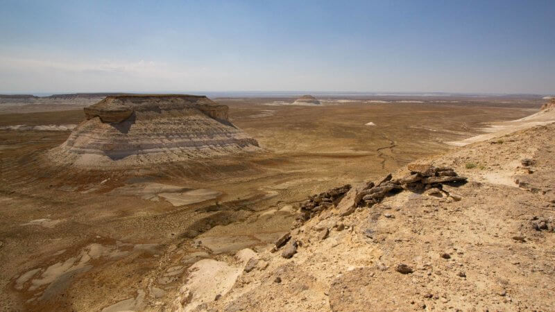 A wide view of the remains of a desert hunting trap overlooking a vast sea of desolate, rocky desert in Kazakhstan.