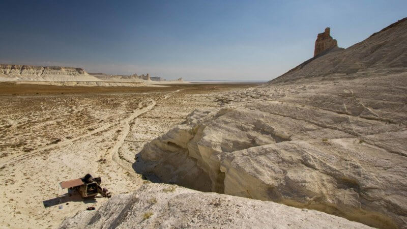 An offroad truck parked beneath limestone cliffs on the edge of a desert.