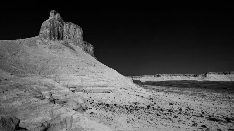 A rocky cliff overlooks an angled slope which leads down towards a Kazakh plateau.
