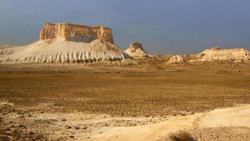 A rock table top mountain with golden cliffs overlooks a desert plateau.