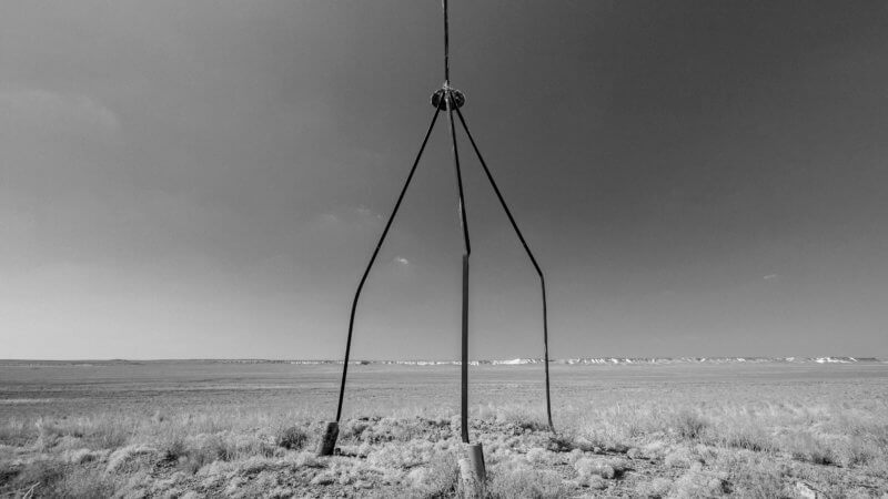 An old Soviet-era survey marker formed out of three tall metal tubes stands in the western Kazakh desert.