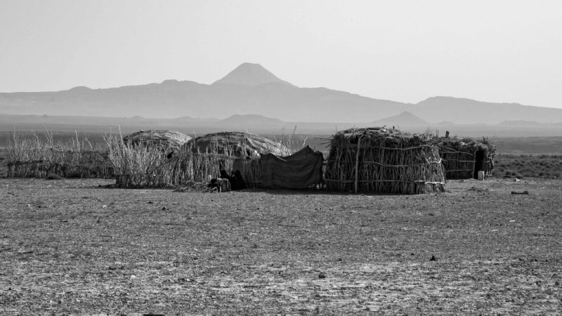 Black and white photo of a traditional Afar settlement with volcano in background.