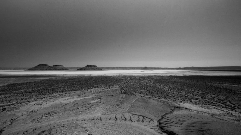 Wide angle view of three hump-shaped mountains in the middle of a giant, dry, and white salt plan near Turkmenistan.