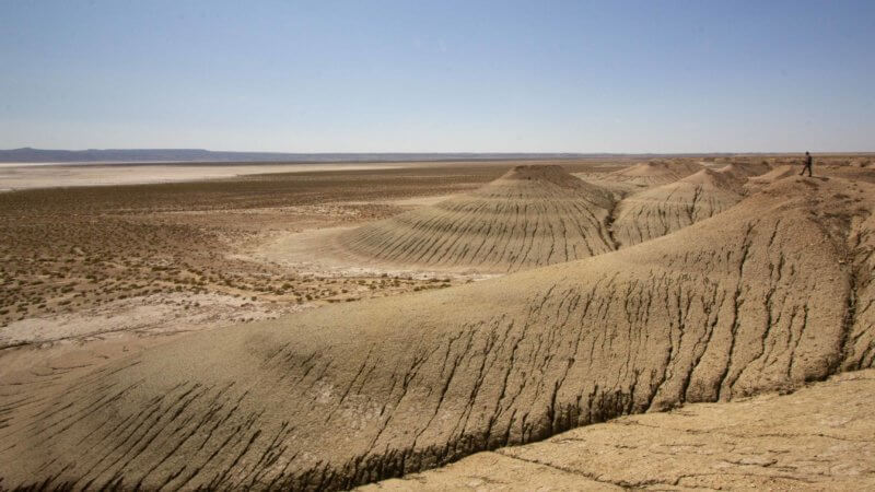 A sloping escarpment descends towards a desolate Ustyurt salt pan.
