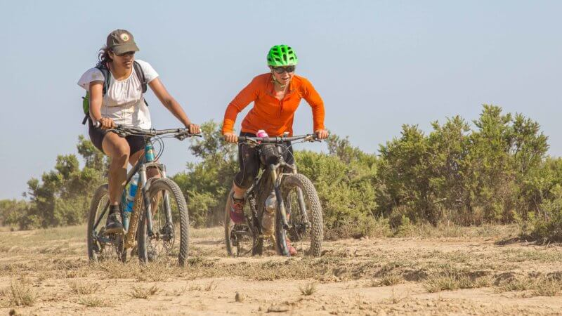 Two cyclists on a sunny day in the Ethiopian desert.