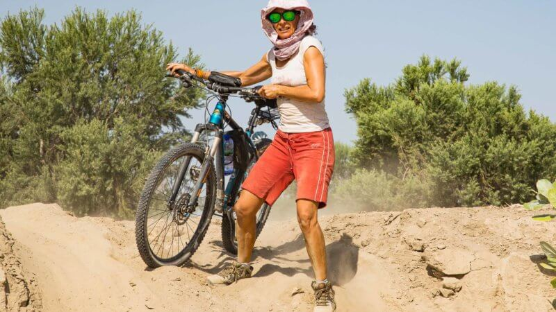 A mountain biker descending down a sand bank with her bicycle.