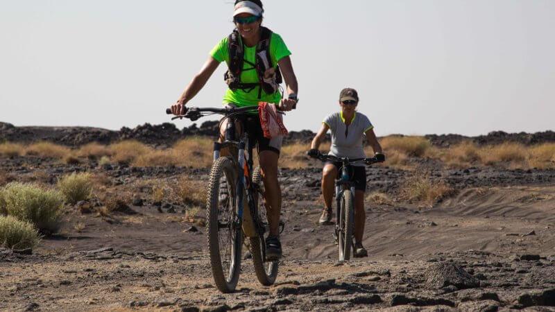 Two women on mountain bikes riding up Erta Ale in Ethiopia.