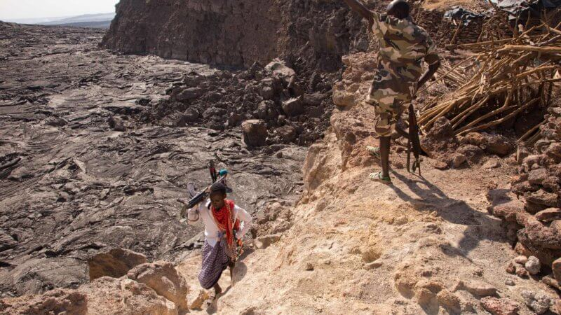 An Afar guide ascends out of the crater as a soldier talks to him from above.