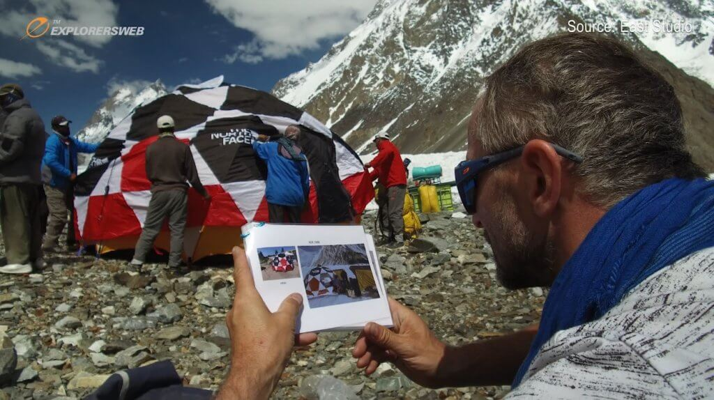 Screenshot of a Polish mountaineer looking on as Pakistani porters assemble their tent in the Karakorum.