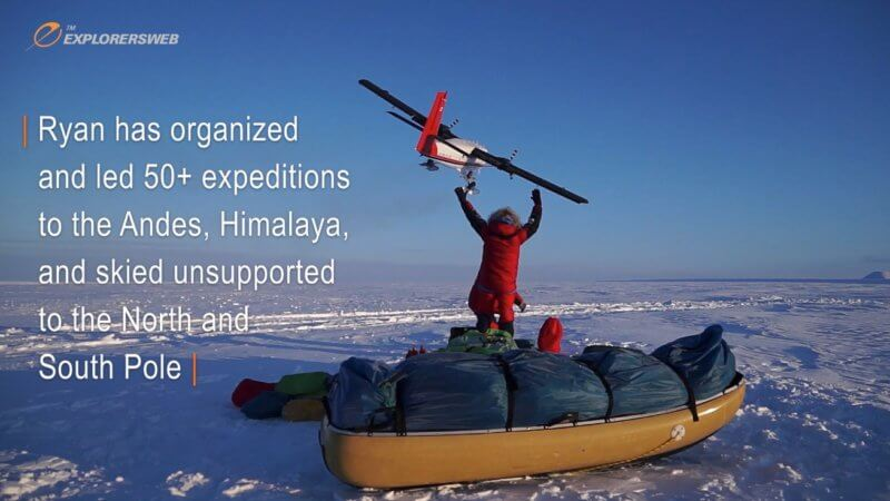 An Arctic explorer stood next to a sled joyously pumps his fists in the air as a plane flies away from him.