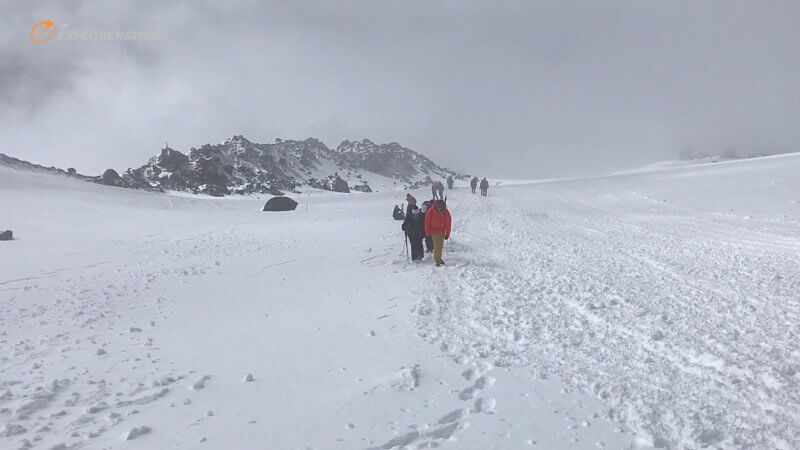 A small group of mountaineers ascend up a snow slope in the fog on Mount Elbrus.