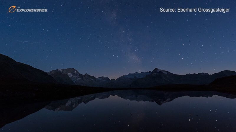 Screenshot of a night timelapse in a mountain range, showing a big lake and the Milky Way.