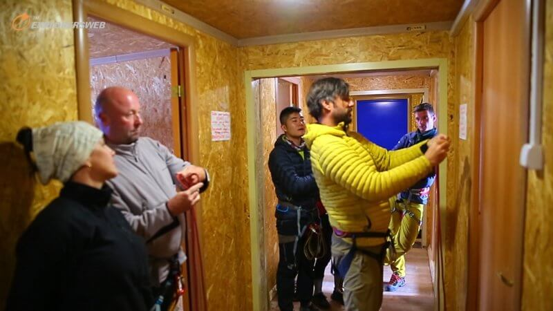 Screenshot of climbers receiving rope tying instructions from a mountain guide, inside of a hut on Mount Elbrus.