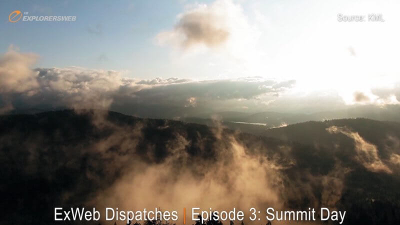 A drone shot flying through forested mountains with sunshine glowing on misty clouds.