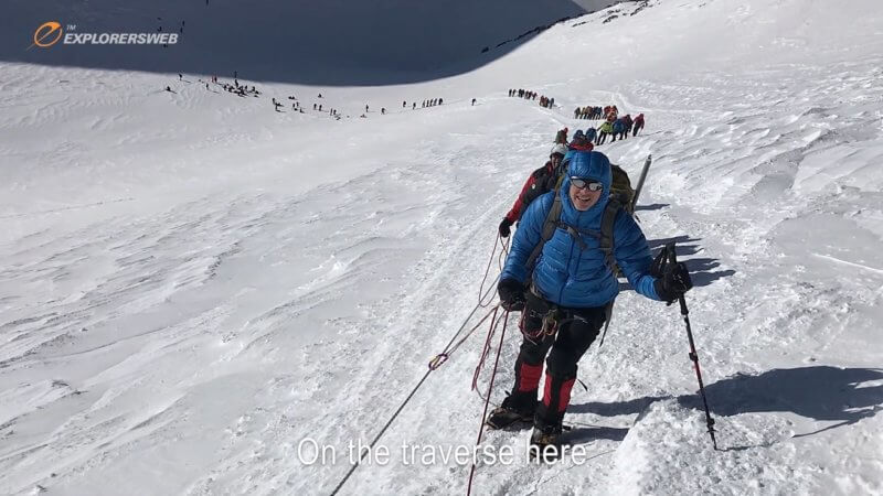 A long trail of mountaineers on a fixed rope ascend up from Mount Elbrus' saddle to the summit.