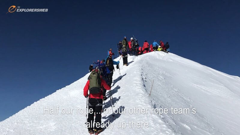 A trail of alpine mountaineers ascend up the final short ridgeline leading to Mount Elbrus' summit.