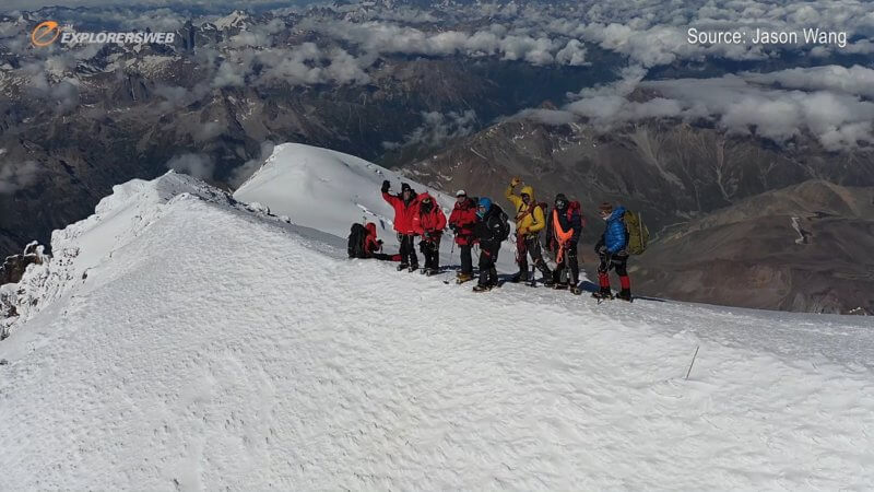 Drone shot of seven mountaineers on the summit of Mount Elbrus on a crystal clear day.