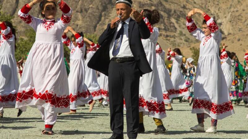 Tajik man singing into microphone and wearing a black suit.