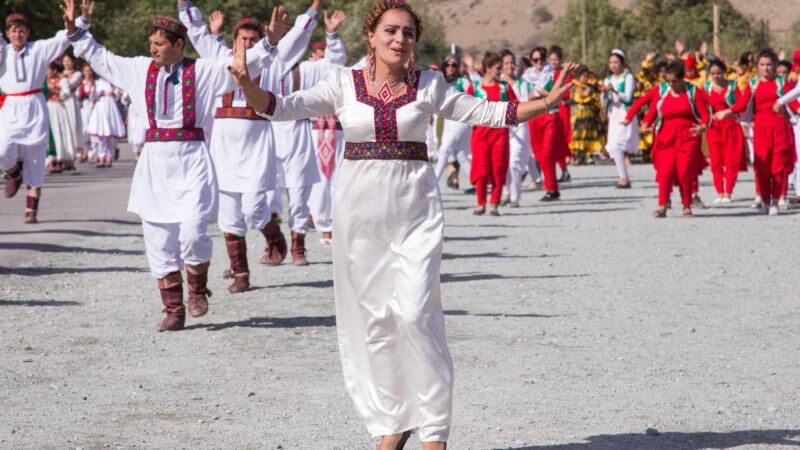 Tajik woman wearing a white coloured traditional outfit singing with dancers behind her.