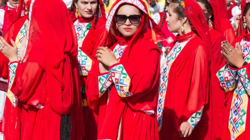 Beautiful Tajik women dressed in red traditional clothes.