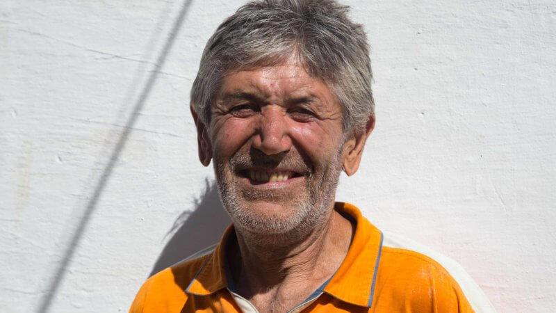 Cheeky smiling guy in Tajikistan wearing a bright yellow shirt.
